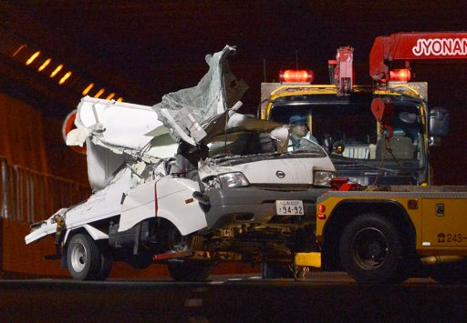 A tow truck hauls the wreckage of a truck, which was crushed in Sunday's accident, out of the Sasago Tunnel on the Chuo Expressway in Koshu, Yamanashi Prefecture, central Japan, early Monday, Dec. 3, 2012. Concrete ceiling panels fell onto moving vehicles deep inside the tunnel, and authorities confirmed nine deaths before suspending rescue work Monday while the roof was being reinforced to prevent more collapses. (AP Photo/Kyodo News)