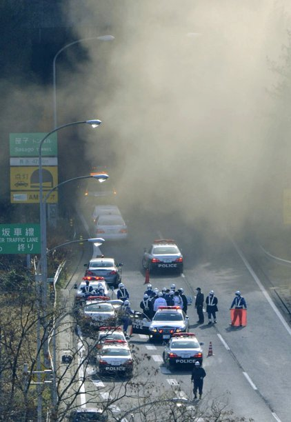 Smoke billows out of the Sasago Tunnel on the Chuo Expressway in Koshu, Yamanashi Prefecture, central Japan, Sunday morning, Dec. 2, 2012. A part of the tunnel collapsed Sunday morning, possibly involving several vehicles and injuring several people, local media said. (AP Photo/Kyodo News)