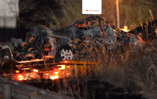 The burnt wreckage of a minivan, which was crushed and caught fire in Sunday's accident, is moved on a transporter out of the Sasago Tunnel on the Chuo Expressway in Koshu, Yamanashi Prefecture, central Japan, early Monday, Dec. 3, 2012. Concrete ceiling panels fell onto moving vehicles deep inside the tunnel, and authorities confirmed nine deaths before suspending rescue work Monday while the roof was being reinforced to prevent more collapses. (AP Photo/Kyodo News)