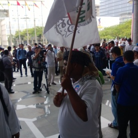 A participant from Nadi Rakyat holding up a flag with the words 'La Ilaha Illallah' at the Palace of Justice on the 22/8/2013.