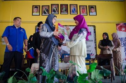 Nor Hafiza Khalid, Pengarah Jabatan Latihan dan Pembangunan dari Pejabat Exco YB Datuk Md Jais Sarday, menerima saguhati dari Rosaini Ahmad, pengetua SMK Tan Sri Mohamed Rahmat semasa program Jelajah Kemerdekaan MPJ.